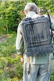 Arbeider het bespuiten van pesticide op de tuin van het land Stock Foto's