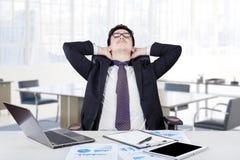 Arbeider het ontspannen in zijn bureauruimte Stock Foto's