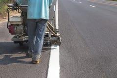 Arbeider het schilderen de verkeerslijn met het bespuiten werpt machine uit Stock Afbeeldingen
