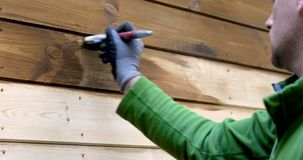 Arbeider het schilderen huis buiten met houten beschermende kleur stock footage