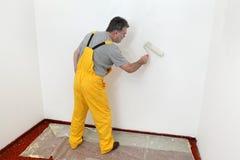 Arbeider het schilderen muur in ruimte royalty-vrije stock afbeelding