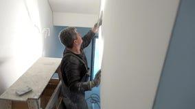 Arbeider het schrobben muur met schuurpapier Mens die oppervlakte voor het schilderen voorbereiden stock video