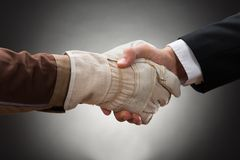 Arbeider het schudden hand met zakenman royalty-vrije stock afbeeldingen