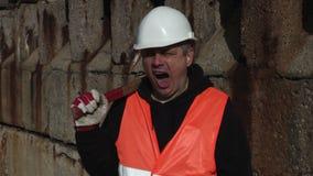 Arbeider met een hamer op zijn schouder stock videobeelden