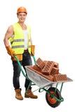 Arbeider met een kruiwagenhoogtepunt van bakstenen Stock Foto