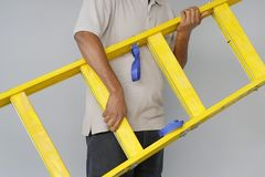 Arbeider met houten ladder stock foto