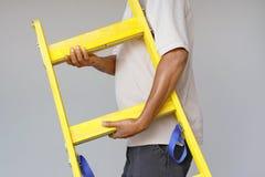 Arbeider met houten ladder stock fotografie