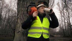 Arbeider met kettingzaag op schouder dichtbij boom het drinken koffie stock footage