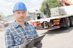 Arbeider met klembord vooraan vrachtwagen stock foto's