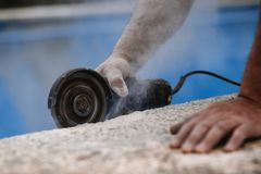 Arbeider met radiale zaag met stof op de lucht met blauwe achtergrond stock foto's