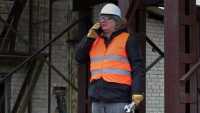 Arbeider met regelbare moersleutel die op celtelefoon spreken stock footage