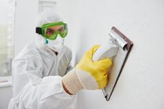Arbeider met schuurmachine bij muur het vullen stock foto