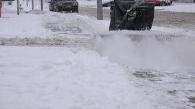 Arbeider met sneeuwblazer schone sneeuw van voetpad op sneeuwstraat bij de winter 4K stock videobeelden