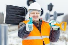 Arbeider met sneeuwschop dichtbij signaalbakens in sneeuwdag Stock Afbeelding