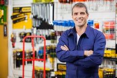 Arbeider met Wapens in Hardwarewinkel die worden gekruist Royalty-vrije Stock Foto's