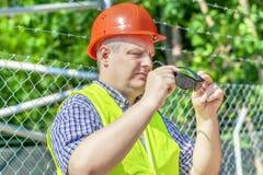 Arbeider met zonnebril dichtbij de omheining Royalty-vrije Stock Foto's