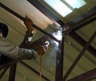 Arbeider ons elektrische lassen verbindende bouw Stock Foto