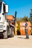 Arbeider op bouwwerf het leegmaken container voor afval van vrachtwagen Stock Fotografie
