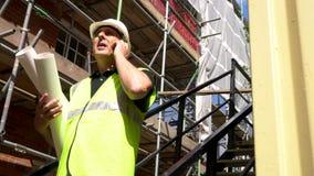 Arbeider op de holdingsbouwtekeningen van het bouwbouwterrein en het spreken op zijn celtelefoon stock videobeelden