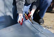 Arbeider op de scharen van het het roestvrije staalblad van de bouwwerfbesnoeiing van om metaal te snijden stock fotografie