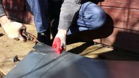 Arbeider op een schaar van het het roestvrije staalblad van de bouwwerfbesnoeiing van om metaal te snijden stock video