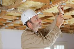 Arbeider op opgeschorte plafonds stock afbeeldingen
