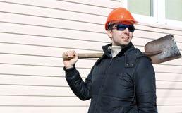 Arbeider in oranje bouwvakker en zonnebril met een schop Royalty-vrije Stock Afbeeldingen