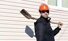 Arbeider in oranje bouwvakker en zonnebril met een schop in zijn hand Royalty-vrije Stock Afbeeldingen