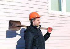 Arbeider in oranje bouwvakker met schop in zijn hand Stock Foto