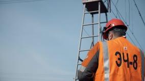 Arbeider in oranje overall en een helm, mening van de rug Hersteller die van de spoorweg de elektrische lijn en zich de toren bev stock video