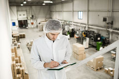 Arbeider in pakhuis voor voedsel verpakking Stock Foto's