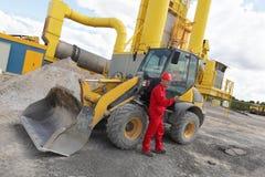 Arbeider in rode eenvormige krijgende massage op mobiele telefoon bij bouwwerf Royalty-vrije Stock Afbeelding