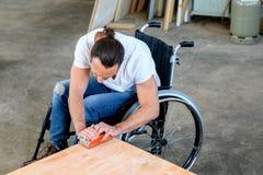 Arbeider in rolstoel in een timmerliedenworkshop stock afbeelding