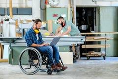 Arbeider in rolstoel in een timmerliedenworkshop met zijn colleagu royalty-vrije stock fotografie