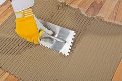 Arbeider toegepaste tegelkleefstof op oude houten vloer Stock Foto's