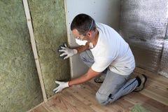 Arbeider in veiligheidsbrillen en de wolisolatie van de ademhalingsapparaat isolerende rots in houten kader voor toekomstige huis royalty-vrije stock foto's