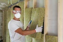 Arbeider in veiligheidsbrillen en wol van de ademhalingsapparaat de isolerende rots Stock Afbeeldingen