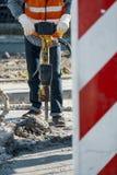 Arbeider in weerspiegelend vest en met boor die asfaltdurin herstellen royalty-vrije stock afbeelding