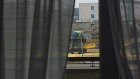 Arbeider Workin door Venster wordt gezien dat stock footage