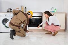 Arbeiders Bespuitende Insecticiden in Front Of Housewife stock fotografie