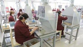 Arbeiders bij een lopende band in munitiefabriek stock footage