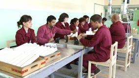 Arbeiders bij een lopende band in munitiefabriek Gezoem uit stock videobeelden