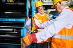 Arbeiders bij moderne fabriek stock afbeeldingen