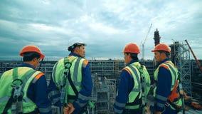 Arbeiders bij raffinaderij als team die, industriële scène op achtergrond bespreken stock footage