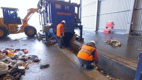 Arbeiders die afval, huisvuil bij een transportband van de recyclingsinstallatie sorteren stock video