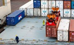 Arbeiders die container controleren die bij dok uploaden Stock Fotografie