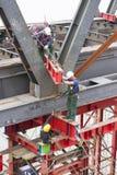 Arbeiders die dragend platform vastmaken aan brug, redactie Stock Afbeelding