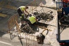 Arbeiders die een gebroken waterpijp op de weg herstellen stock afbeelding