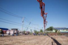 Arbeiders die een houten spatel voor cement na het Gieten van ready-mixed beton door boom en concrete pomp gebruiken te plaatsen stock foto