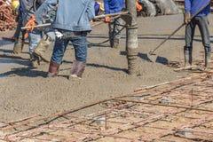Arbeiders die een houten spatel voor cement na het Gieten van ready-mixed beton gebruiken royalty-vrije stock afbeeldingen